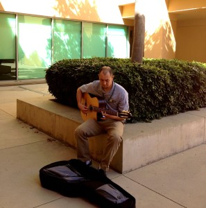 Arts and Sciences teacher Chris Irwin strums his guitar in the D. Diane Anderson Family Humanities Building courtyard. September 19 2013. Photographer: Erika Lynn-Green