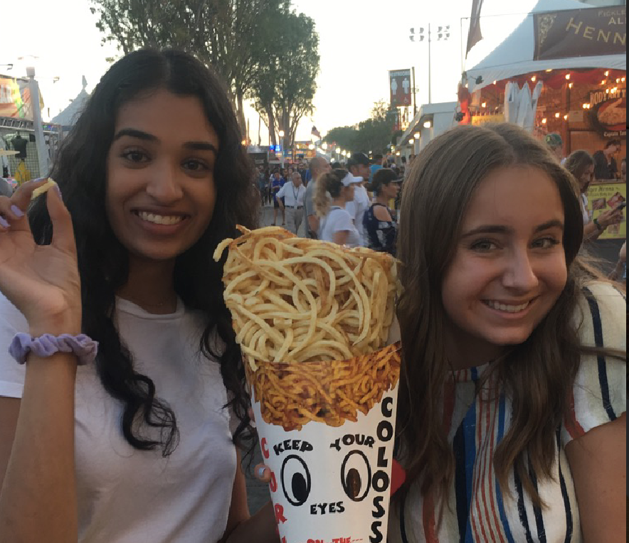 Seniors+Ishani+Patel+and+Miranda+deBruyne+share+some+of+the+famous+OC+Fair+curly+fries