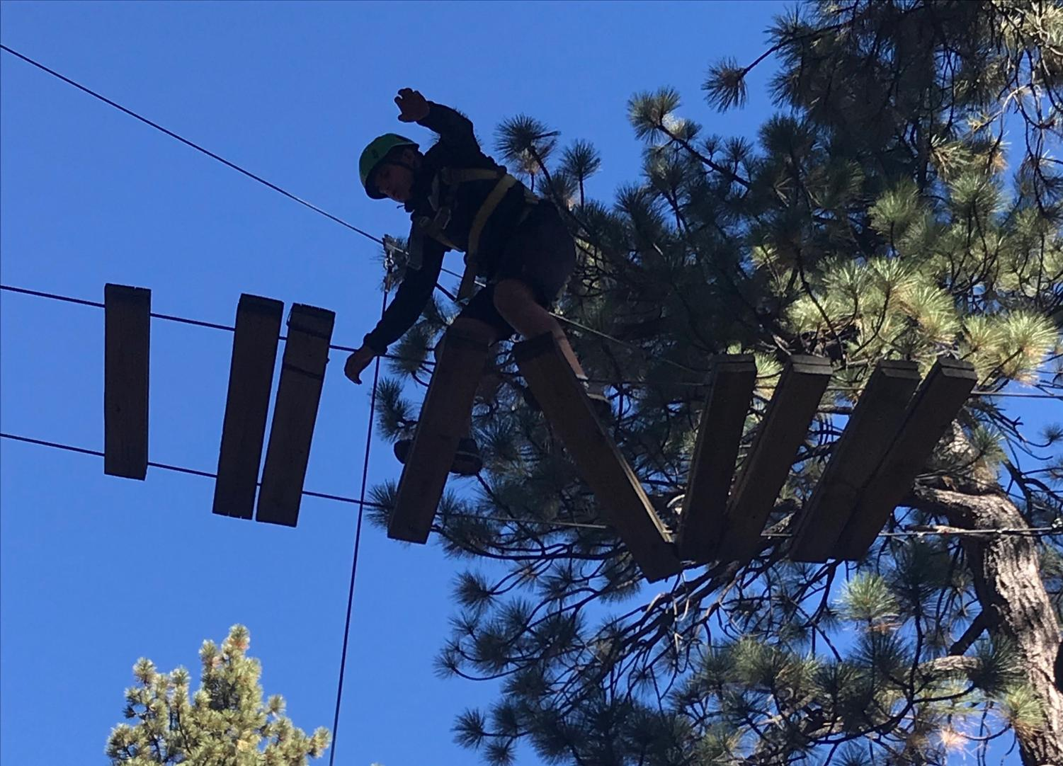 Adam Hayek walks across a suspended ladder on the high ropes course