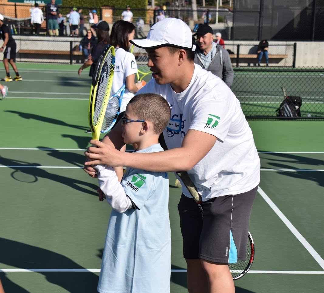 Senior Ryan Ha helps an ACEing Autism participant learn how to hit a solid forehand.