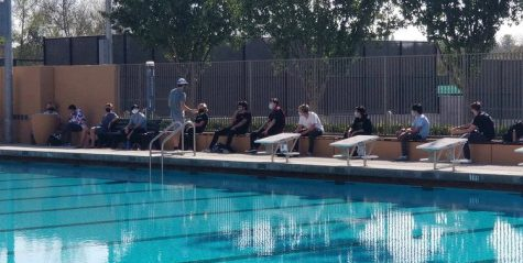 The water polo team has a socially distanced team meeting during practice.