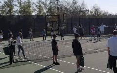 Tennis team players gather around the tennis courts during practice.