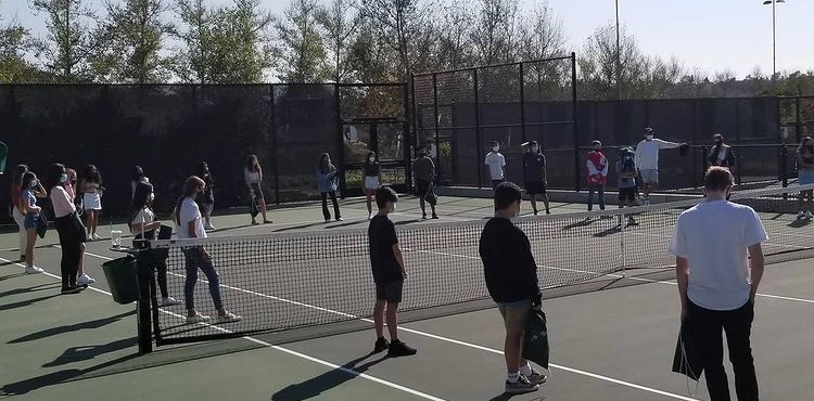 Tennis+team+players+gather+around+the+tennis+courts+during+practice.+